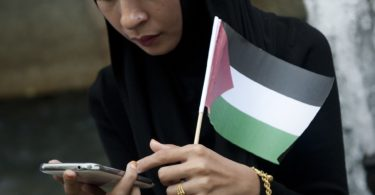 A protestor check her phone as she holds a Palestinian flag outside the Israeli embassy in Bangkok, during a demonstration against Israeli air strikes on Gaza, on July 15, 2014. Israel pressed its campaign of punishing raids on Gaza, and the Palestinian death toll rose to 172, with another 1,230 wounded. AFP PHOTO/ Nicolas ASFOURI        (Photo credit should read NICOLAS ASFOURI/AFP/Getty Images)